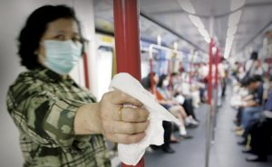 WOMAN WEARING MASK USES TISSUE PAPER TO AVOID CONTACT WITH SARS ONTRAIN IN HONG KONG.